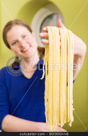 Homemade Pasta Fettuccine Detail stock photo, A proud young woman with fresh homemade fettuccine - shallow depth of field with focus on the pasta by Tyler Olson