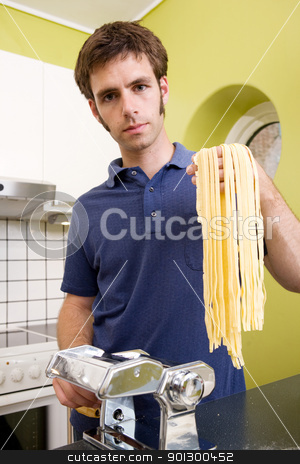 Homemade Pasta Fettuccine stock photo, A proud young man with fresh homemade fettuccine looks at the camera- shallow depth of field with focus on the pasta by Tyler Olson
