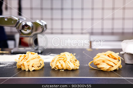 Fresh Fettuccine stock photo, A detail of homemade fettuccine ready to be boiled by Tyler Olson