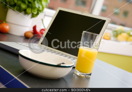 Online Breakfast stock photo, A computer in the kitchen with a bowl of soupr or cereal and orange juice - shallow depth of field with focus on juice by Tyler Olson