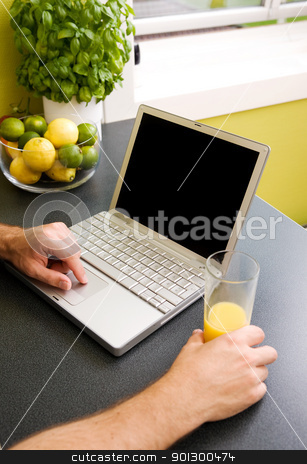 Kitchen Computer stock photo, A computer in the kitchen with a male hand using the touch pad.  The laptop has a completely black screen for easy editing. by Tyler Olson