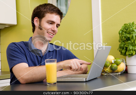 Funny Computer stock photo, A young male using a laptop computer in the kicthen, smiling and laughing at what he sees by Tyler Olson