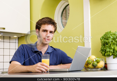Kitchen Computer stock photo, A young male using a laptop computer in the kicthen and smiling at the camera. by Tyler Olson