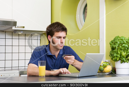 Online Shopping in Kitchen stock photo, A young male shops online with a credit card in his kitchen. by Tyler Olson