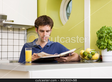 Recipe Book stock photo, A young man in the kitchen looking at recipes. by Tyler Olson