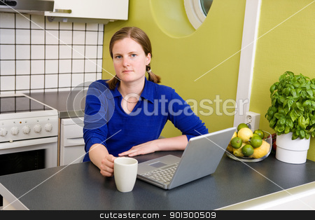 Young woman with Computer and Coffee stock photo, A young woman sitting in the kitchen with a coffee and a computer looking at the camera. by Tyler Olson