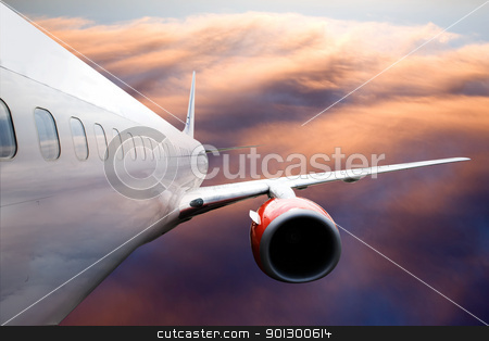 Airplane in Flight stock photo, An airplane accending over a dramatic cloudscape. by Tyler Olson