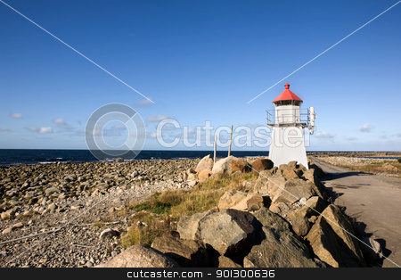 Small Lighthouse stock photo, A small lighthouse on a rocky point by Tyler Olson