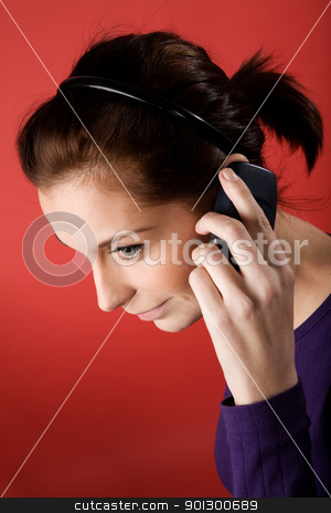 Listen on Cell Phone stock photo, A young female listening on a cell phone. isolated on red. by Tyler Olson