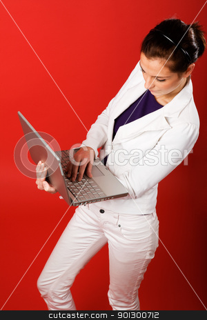 Red Studio Laptop stock photo, A young business woman or student using a laptop by Tyler Olson