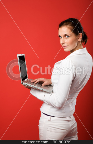 Female with Computer on Red stock photo, A young woman typing on a laptop computer isolated on red by Tyler Olson