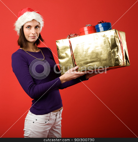 Giving a Gift stock photo, A young woman with a present isolated on red by Tyler Olson