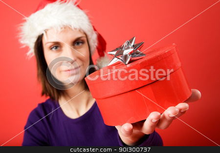 Small Gift stock photo, A young woman with a present isolated on red - shallow depth of field with the focus on the present box. by Tyler Olson