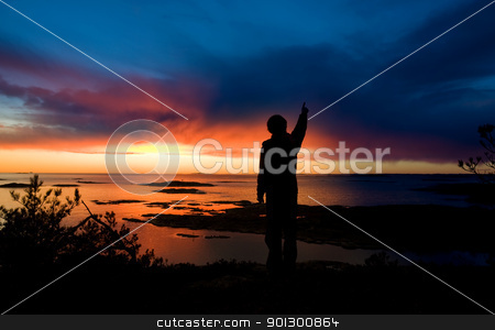 Ocean Discovery stock photo, A person standing by the ocean pointing into the distance by Tyler Olson