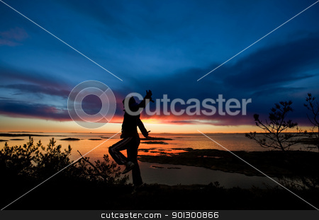 Ocean Cheer stock photo, A person running by the ocean raising their arms in celebration by Tyler Olson