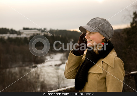 Young Woman with Phone stock photo, A young woman outside in winter talking on a cell phone by Tyler Olson