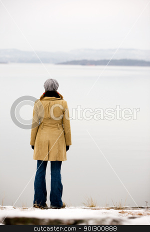 Calm by Ocean stock photo, A young woman standing by the ocean in winter by Tyler Olson