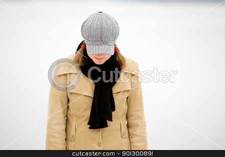 Shy Winter Woman stock photo, A young woman standing by the ocean in winter with head down by Tyler Olson