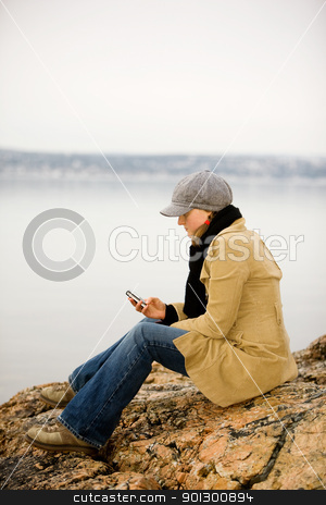Cellphone by Ocean stock photo, A young woman sitting by the ocean using a cell phone by Tyler Olson