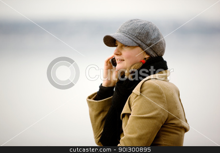Winter Cell Phone stock photo, A young woman talking on a cell phone in winter. by Tyler Olson