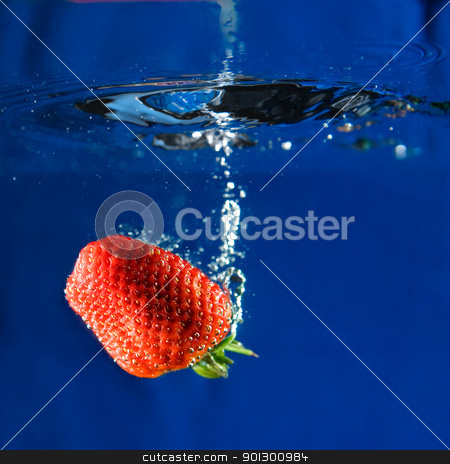 Fresh Strawberry stock photo, A fresh strawberry dropping in water. by Tyler Olson