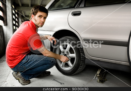 Tire Repair stock photo, A male chaning a tire on a car by Tyler Olson