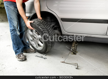 Tire Change stock photo, A male changing a tire on a car in a garage by Tyler Olson