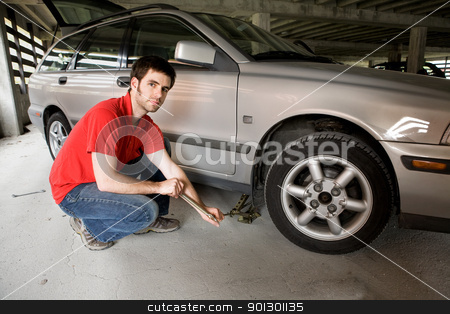 Tire Change stock photo, A male in a red shirt changing the front tire on a car by Tyler Olson