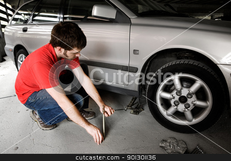 Auto Repair stock photo, A male jacks up a car in a garage - fixing the wheel by Tyler Olson
