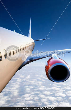 Airplane in Flight stock photo, An airplane in flight over a blue sky by Tyler Olson