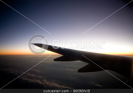 Sunset Airplane stock photo, A wing on an airplane in flight at sunset by Tyler Olson