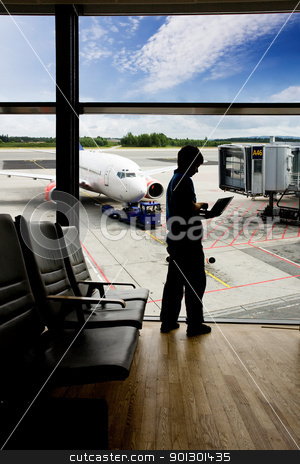 Airport Terminal Laptop stock photo, A young man using a laptop in an airport terminal by Tyler Olson