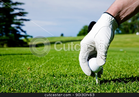 Golf Tee Hand stock photo, A golfer sets up a tee at a driving range by Tyler Olson