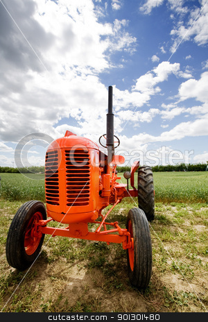 Old Retro Tractor stock photo, An old orange retro tractor in a field by Tyler Olson