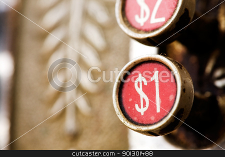 One Dollar Button stock photo, A one dollar button on a retro cash register - shallow depth of field. by Tyler Olson