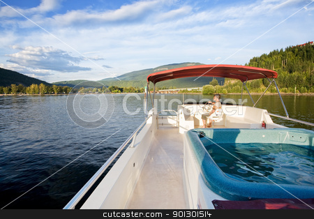 Luxury Yacht stock photo, A young male driving a cruise yacht by Tyler Olson
