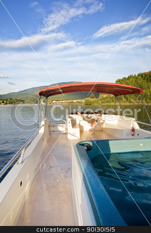 Luxury Boat Owner stock photo, A young male driving a house boat from the upper helm. by Tyler Olson