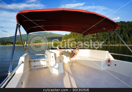 House boat on Lake stock photo, A young male driving a house boat from the upper helm. by Tyler Olson