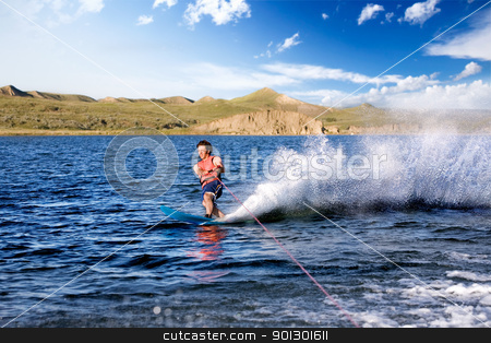 Waterskiing stock photo, A male waterskiing on a lake in the evening by Tyler Olson