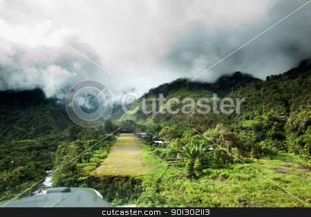 Mountain Village Runway stock photo, A runway in a mountain village - approachnig with a small aircraft by Tyler Olson
