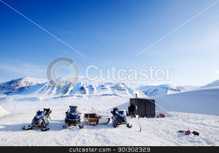 Winter Base Camp stock photo, People preparing snowmobiles for an expedition through through winter conditions by Tyler Olson
