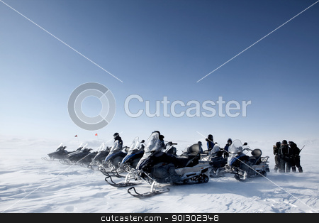 Snowmobile Group stock photo, A group of snowmobiles travelling accross a barren winter landscape by Tyler Olson