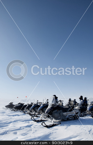 Snowmobile Trip stock photo, A large group of snowmobiles on a barren winter landscape by Tyler Olson