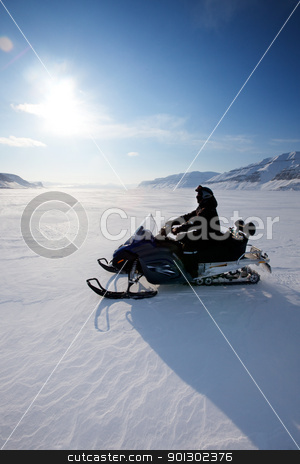 Snowmobile stock photo, A snowmobile on frozen ice on a barren winter landscape by Tyler Olson