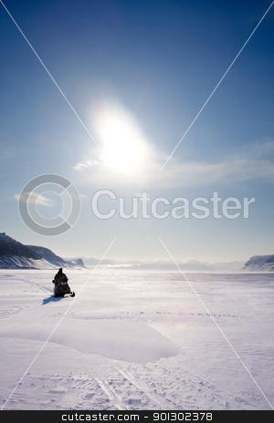 Mountain Winter Landscape stock photo, A snowmobile on frozen ice on a barren winter landscape by Tyler Olson