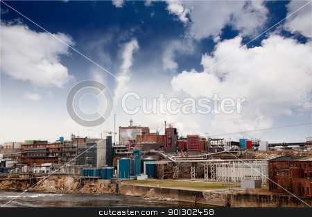 Industry stock photo, A mesh of buildings on a river billowing smoke into the sky by Tyler Olson