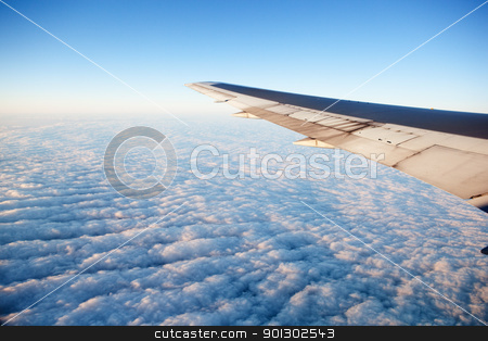 Airplane in wing stock photo, A wing of an airplane flying of a cloudscape by Tyler Olson