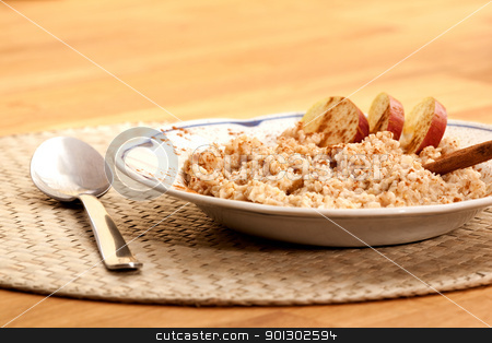 Apple Cinnamon Porridge stock photo, A bowl of apple cinnamon porridge on a wooden table. by Tyler Olson
