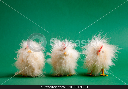 Easter Chicken stock photo, Three funny little easter decorations lined up on a green background by Tyler Olson