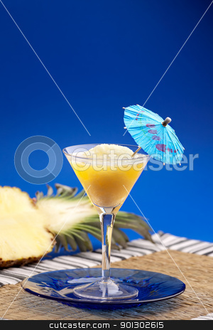Pineapple Smoothie stock photo, A pineapple smothie isolated over blue by Tyler Olson
